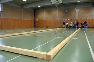 Die mobile Indoor-Bocciabahn wird aus zwei Vierkanthölzern in der Breite und neun in der Länge zusammengesteckt.©Freya S. Altmüller, i.A. d. Stadt Marburg