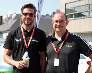 Straßenradrennfahrer Andreas Stauff (links) begleitete den Gewinnspiel-Sieger Mark Losert an Bord eines offiziellen In-Race-Fahrzeuges im Renntross nach Göttingen.©Simone Schwalm, Stadt Marburg